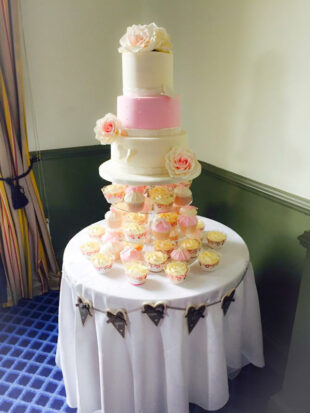 Three tier stacked wedding cake with hand made roses and cupcakes to match stoke on trent