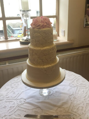 Three tier classic lace wedding cake with hand made roses on the top stoke on trent