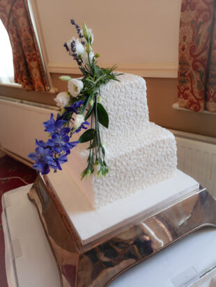 Two tier square wedding cake with real flowers with pipped details